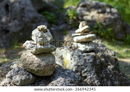 Stack of pebble stones by a stream in a forest  - stock photo