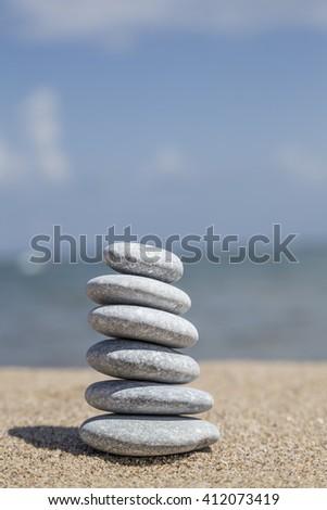 stack of pebble stones on balance on sandy beach - stock photo