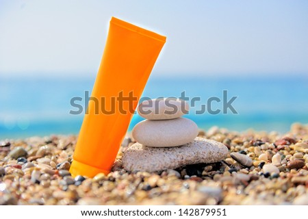 Stack of pebbles and cream at the beach - stock photo