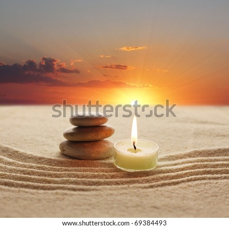 Stack of pebbles and light candle - stock photo