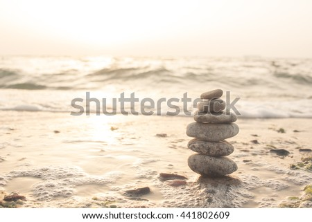 Stack of pebbles  at the beach on the sunlight background - stock photo