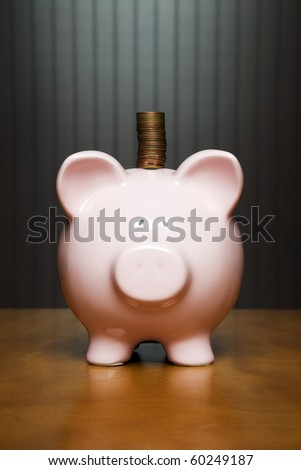 Stack of pennies placed on a piggy bank - stock photo