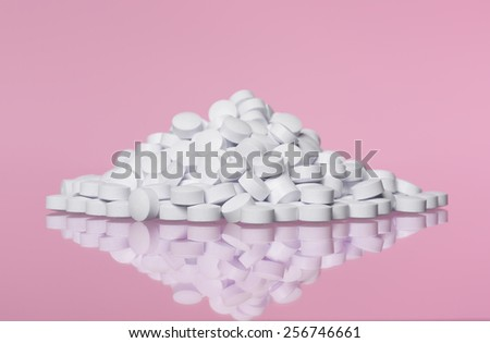 Stack of pills towards pink background - stock photo