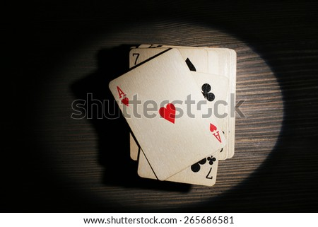 Stack of playing cards in light on wooden table, top view - stock photo