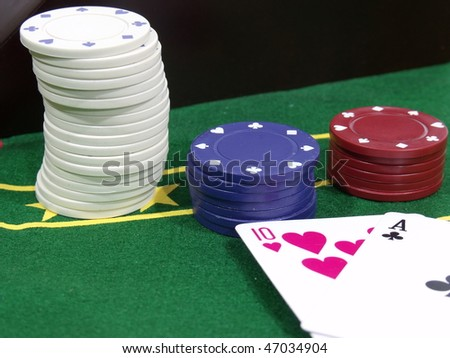 Stack of poker chips next to two playing cards on a poker table