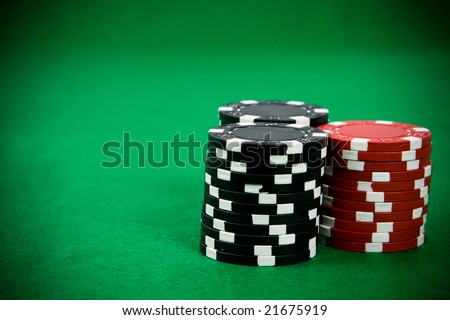 Stack of poker chips on green background.