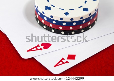 Stack of poker chips placed on top of a pair of ace. - stock photo