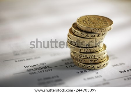 Stack of pound coins on financial figures balance sheet - stock photo