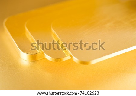 stack of pure gold ingots on a golden background - stock photo