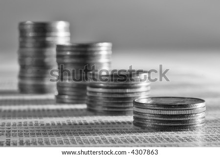 Stack of quarters on the stock report section of the newspaper - stock photo