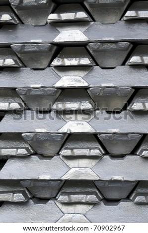 Stack of raw aluminum ingots in aluminum profiles factory - stock photo