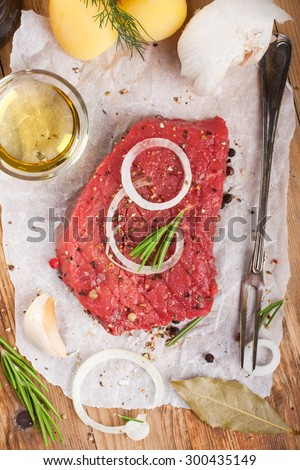 Stack of raw beef steaks and spices on old wooden background.  Healthy food concept. Selective focus. Top view.  - stock photo