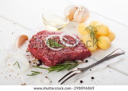 Stack of raw beef steaks and spices over white.  Healthy food concept. Selective focus. - stock photo