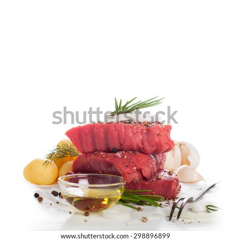 Stack of raw beef steaks and spices over white.  Healthy food concept with copy space for text. Selective focus. - stock photo
