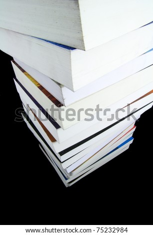 Stack of real books isolated on black background - stock photo