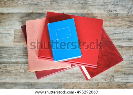 stack of red and blue books on the floor