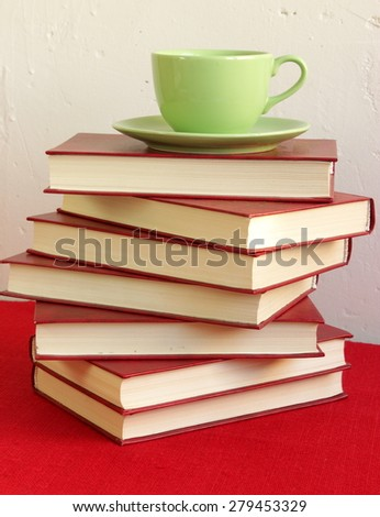 Stack of red books an green cup of coffee