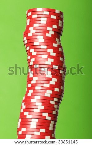 Stack of red casino chips against green background - stock photo