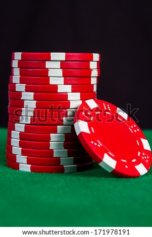 Stack of red chips on a green playing table with black background - stock photo