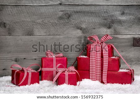 Stack of red Christmas gift boxes with snow on grey wooden background for a greeting card or shopping, coupon.. - stock photo