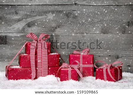 Stack of red Christmas gifts,snow on grey wooden background. - stock photo