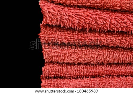 Stack of red towels on a black background.