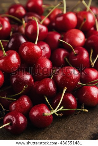Stack of ripe red cherries. Dark food photography. Shallow focus