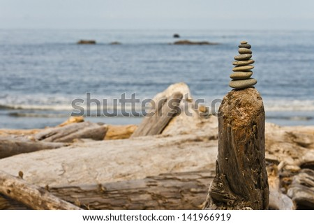 Stack of Rocks at Sea Shore on Driftwood - stock photo