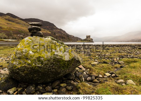 Stack of rocks in front of Eilean Donan Castle - stock photo