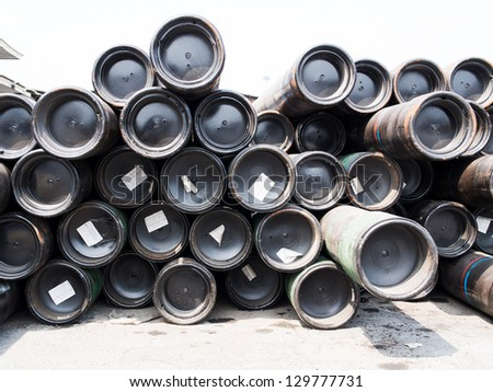 stack of rounded steel pipes at port.
