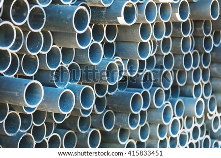 stack of rounded steel pipes with soft focus perspective - stock photo