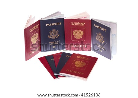 Stack of russian and US passports on white isolated - stock photo