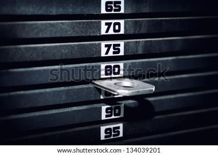 Stack of rusty metal weights in gym bodybuilding equipment - stock photo