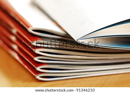 stack of same magazines with red covers closeup