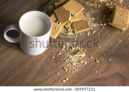 Stack of several sweet rectangle crisp cookies on wooden table with cup of milk - stock photo