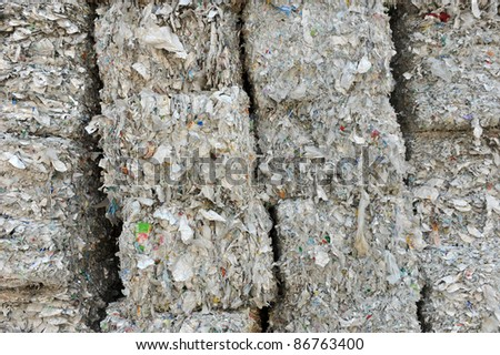 stack of shredded paper at recycling plant. - stock photo
