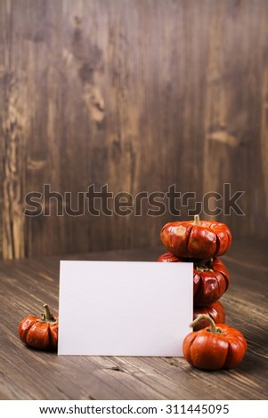 Stack of small orange decorative pumpkins with a card for text. Halloween or thanksgiving day concept. Vintage style, selective focus. Toned image - stock photo