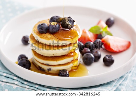 Stack of small pancakes with fresh berries and syrup - stock photo