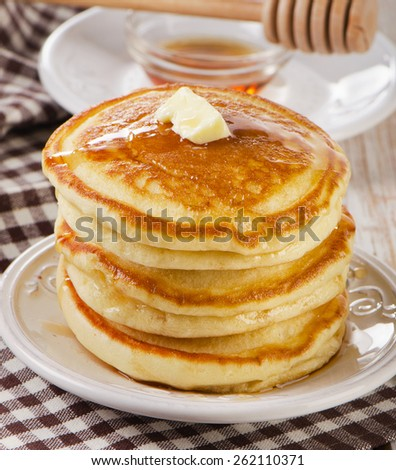 Stack of Small pancakes with maple syrup .
