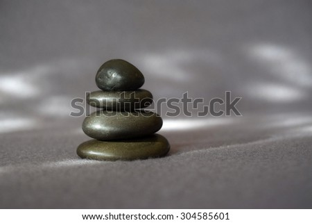 Stack of smooth stones perfectly balanced on a serene grey background - stock photo