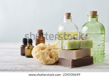 Stack of soap bars with sponge and bottles on light background - stock photo