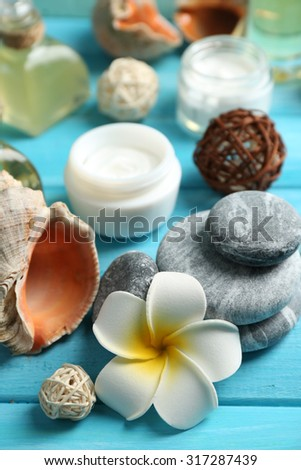 Stack of spa stones and spa treatments on color wooden background - stock photo