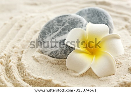Stack of spa stones on sand background - stock photo
