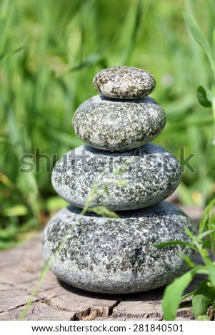 Stack of spa stones over green grass background