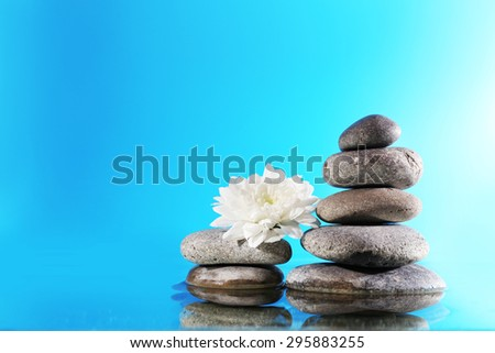 Stack of spa stones with flower  on blue background