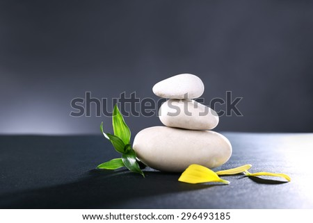 Stack of spa stones with green leaves and flower petals on dark background - stock photo