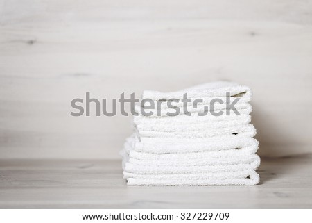 stack of spa towels on white wooden table - stock photo