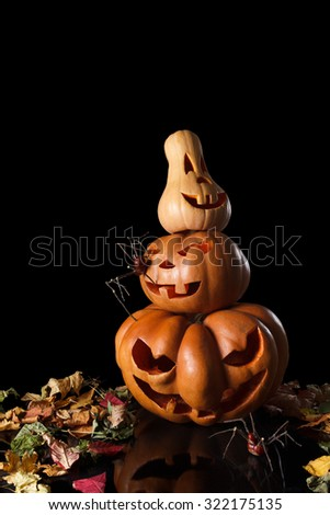 Stack of spooky Halloween pumpkin with fallen leaves, a terrible fire and reflections. Isolated on black background - stock photo