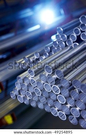 stack of steel pipes with blue light - stock photo