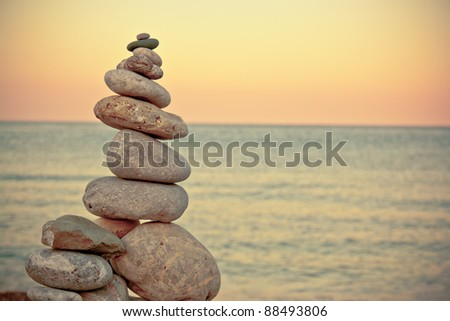 Stack of stones at the beach during sunset - stock photo